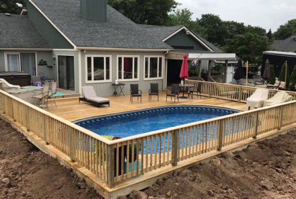 Inground pool with wooden deck and railing